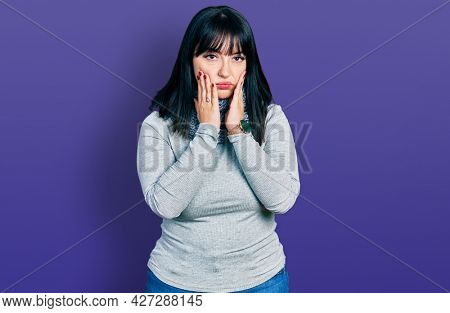Young hispanic plus size woman wearing winter scarf tired hands covering face, depression and sadness, upset and irritated for problem