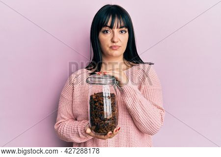 Young hispanic woman holding jar of raisins relaxed with serious expression on face. simple and natural looking at the camera.