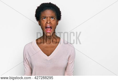 Young african american girl wearing casual clothes angry and mad screaming frustrated and furious, shouting with anger. rage and aggressive concept.