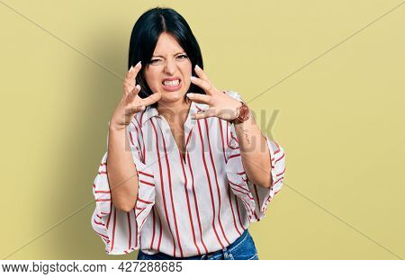 Young hispanic girl wearing casual clothes shouting frustrated with rage, hands trying to strangle, yelling mad