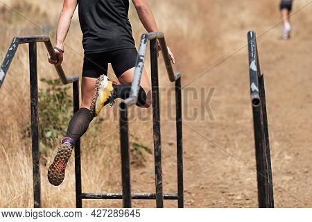 Participant In Extreme Obstacle Race Climbing Over Hurdle