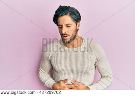 Young hispanic man wearing casual winter sweater with hand on stomach because nausea, painful disease feeling unwell. ache concept.