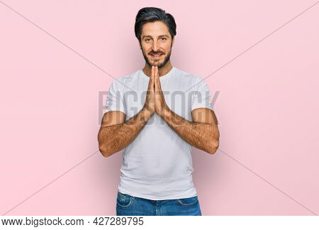 Young hispanic man wearing casual white t shirt praying with hands together asking for forgiveness smiling confident.