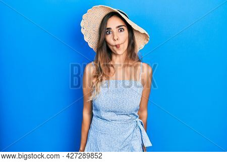 Young hispanic girl wearing summer hat making fish face with lips, crazy and comical gesture. funny expression.