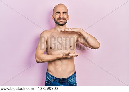 Young bald man standing shirtless gesturing with hands showing big and large size sign, measure symbol. smiling looking at the camera. measuring concept.