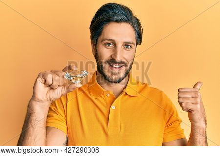 Young hispanic man holding brilliant diamond stone pointing thumb up to the side smiling happy with open mouth