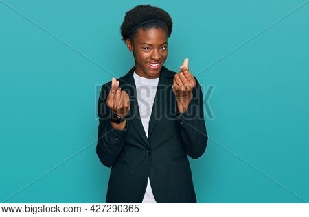 Young african american girl wearing business clothes doing money gesture with hands, asking for salary payment, millionaire business