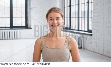 Attractive blonde young woman wearing stylish light beige tracksuit smiles to camera standing in spacious yoga studio close view