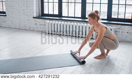 Slim blonde barefoot sportswoman in light beige tracksuit rolls rubber mat after training near large window in spacious yoga studio