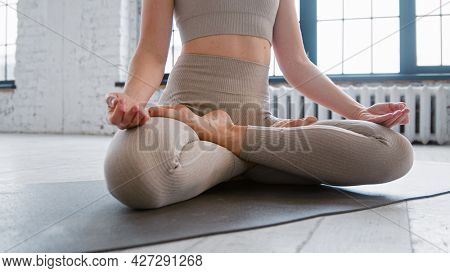 Pretty relaxed young woman in sportswear does yoga breathing exercises sitting in full padma asana in spacious studio close view