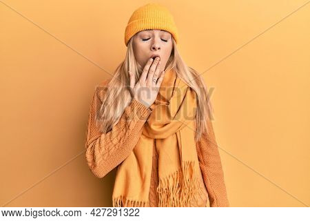 Young caucasian woman wearing wool winter sweater and cap bored yawning tired covering mouth with hand. restless and sleepiness.