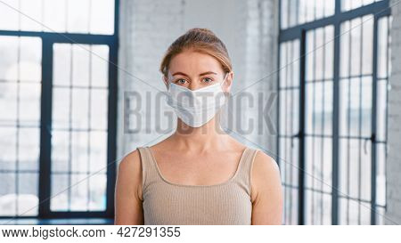 Young lady trainer in tracksuit takes off protective mask looking into camera in spacious studio with windows closeup