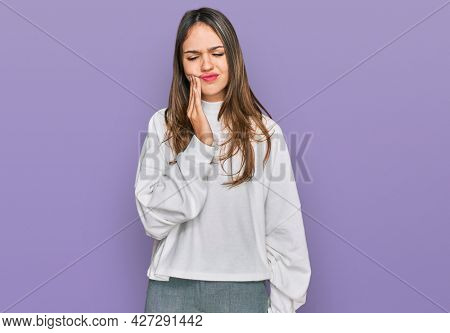 Young brunette woman wearing casual turtleneck sweater touching mouth with hand with painful expression because of toothache or dental illness on teeth. dentist