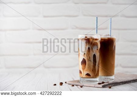 Iced Coffee Latte Cappuccino In A Tall Glass With Cream Or Milk Andcoffeebeans And Straws On A Whi