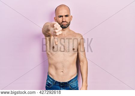 Young bald man standing shirtless looking unhappy and angry showing rejection and negative with thumbs down gesture. bad expression.