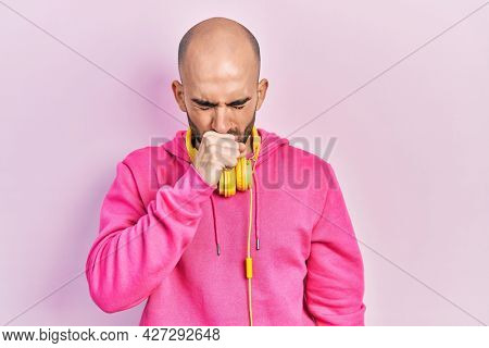 Young bald man wearing gym clothes and using headphones feeling unwell and coughing as symptom for cold or bronchitis. health care concept.