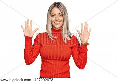 Beautiful blonde woman wearing casual clothes showing and pointing up with fingers number ten while smiling confident and happy.