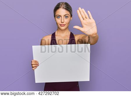 Beautiful blonde woman wearing sportswear holding white banner with open hand doing stop sign with serious and confident expression, defense gesture