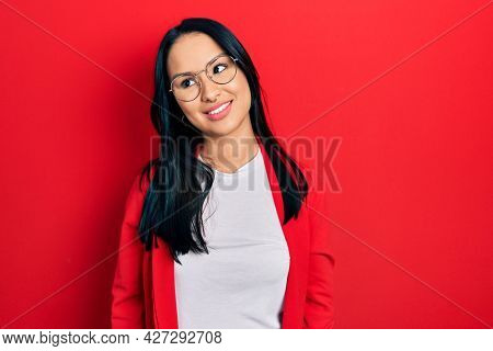 Beautiful hispanic woman with nose piercing wearing casual look and glasses looking away to side with smile on face, natural expression. laughing confident.