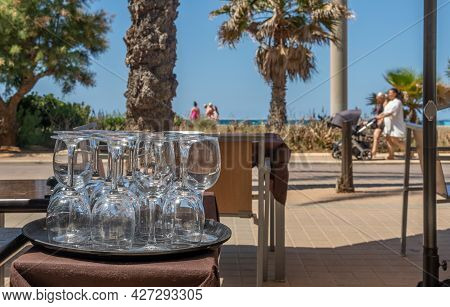 Glass Wine Glasses Geometrically Mounted On An Outdoor Table At A Restaurant On The Beach Promenade