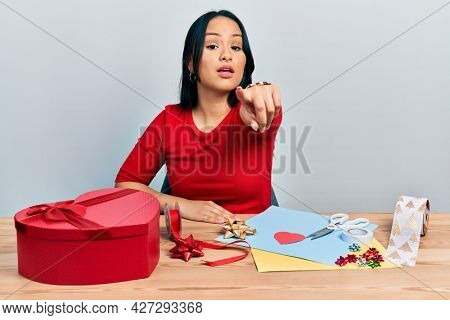 Beautiful hispanic woman with nose piercing doing handcraft creative decoration pointing displeased and frustrated to the camera, angry and furious with you
