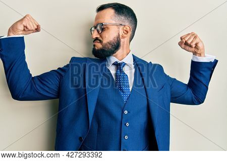 Young man with beard wearing business suit and tie showing arms muscles smiling proud. fitness concept.