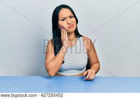 Beautiful hispanic woman with nose piercing sitting on the table touching mouth with hand with painful expression because of toothache or dental illness on teeth. dentist