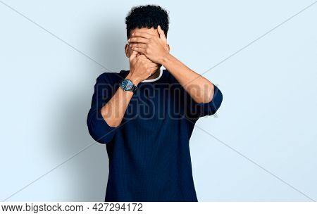 Young african american man wearing casual clothes covering eyes and mouth with hands, surprised and shocked. hiding emotion