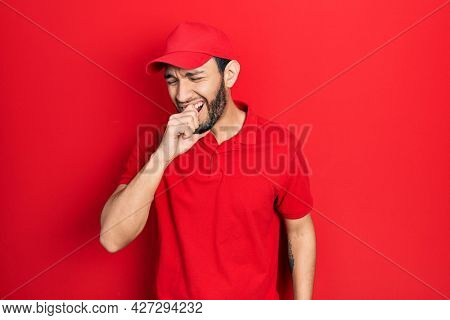 Hispanic man with beard wearing delivery uniform and cap feeling unwell and coughing as symptom for cold or bronchitis. health care concept.