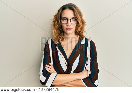 Young caucasian woman wearing business shirt and glasses relaxed with serious expression on face. simple and natural looking at the camera.