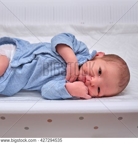 A Happy Newborn Baby In Blue Clothes Smiles Lying On The Changing Table