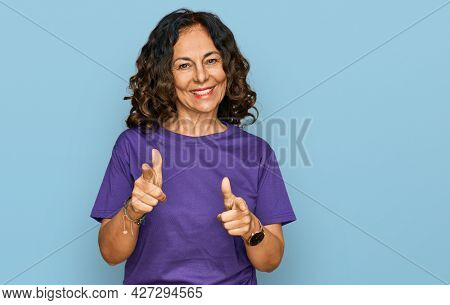 Middle age hispanic woman wearing casual clothes pointing fingers to camera with happy and funny face. good energy and vibes.