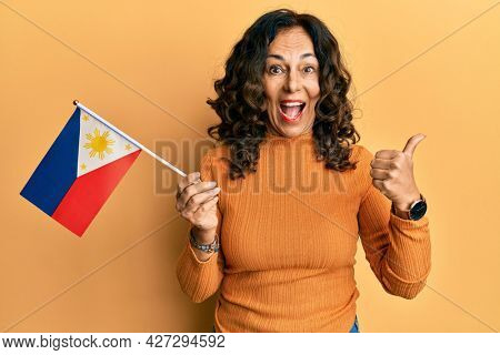 Middle age hispanic woman holding philippines flag pointing thumb up to the side smiling happy with open mouth