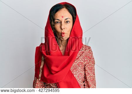 Middle age hispanic woman wearing tradition sherwani saree clothes making fish face with lips, crazy and comical gesture. funny expression.