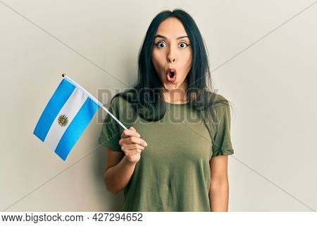 Young hispanic girl holding argentina flag scared and amazed with open mouth for surprise, disbelief face