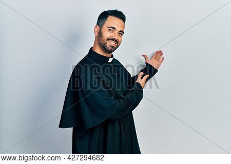 Handsome hispanic man with beard wearing catholic priest robe inviting to enter smiling natural with open hand