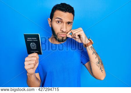 Hispanic man with beard holding italy passport mouth and lips shut as zip with fingers. secret and silent, taboo talking
