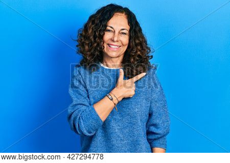 Middle age hispanic woman wearing casual clothes cheerful with a smile of face pointing with hand and finger up to the side with happy and natural expression on face