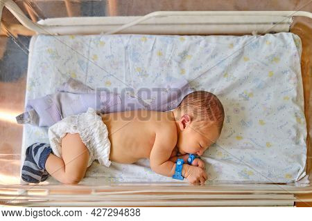 A Newborn Baby With A Maternity Hospital Bracelet On His Arm Is Sleeping In A Crib. A Newly Born Chi