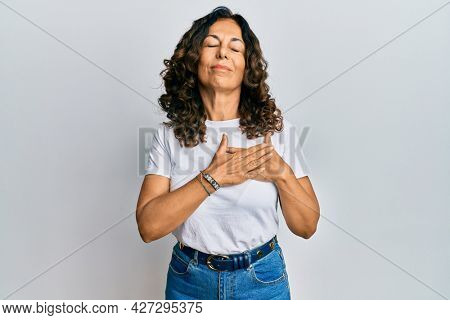 Middle age hispanic woman wearing casual white t shirt smiling with hands on chest with closed eyes and grateful gesture on face. health concept.