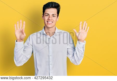 Young hispanic business man wearing business clothes showing and pointing up with fingers number ten while smiling confident and happy.