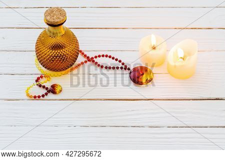 Magic Potion And Amber Necklace On White Wooden Background