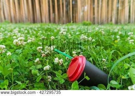 A Black Paper Coffee Cup With A Straw Is Thrown Into The Green Grass. Environmental Pollution With H