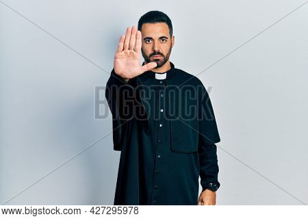 Handsome hispanic man with beard wearing catholic priest robe doing stop sing with palm of the hand. warning expression with negative and serious gesture on the face.