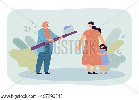 Mother And Daughter At Dentists Appointment. Female Doctor Holding Huge Toothbrush With Toothpaste,