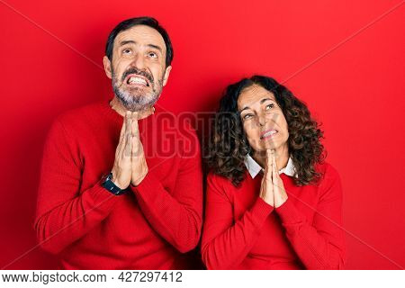 Middle age couple of hispanic woman and man hugging and standing together begging and praying with hands together with hope expression on face very emotional and worried. begging.