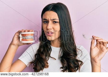 Young hispanic woman holding invisible aligner orthodontic and braces clueless and confused expression. doubt concept.