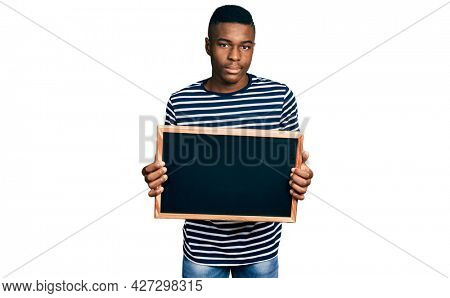 Young african american man holding blackboard relaxed with serious expression on face. simple and natural looking at the camera.