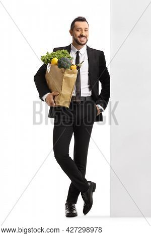 Full length portrait of a businessman with a grocery bag leaning on a wall isolated on white background