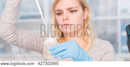 Young attractive woman work with PCR dispenser in  the laboratory of genetics